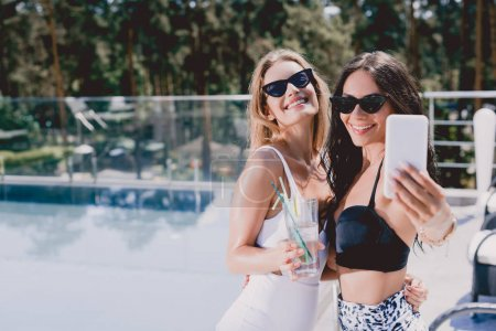 Photo for Sexy and smiling brunette and blonde women in swimsuits taking selfie near swimming pool - Royalty Free Image