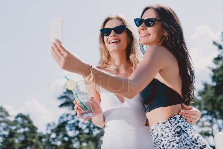 Photo for Low angle view of happy brunette and blonde women in swimsuits taking selfie - Royalty Free Image