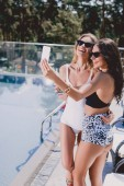 sexy and happy brunette and blonde women in swimsuits taking selfie near swimming pool
