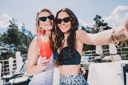 Photo for Beautiful and happy brunette and blonde women with strawberry cocktail - Royalty Free Image