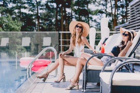 Photo pour Filles heureuses sexy dans des maillots de bain bronzer près de la piscine - image libre de droit