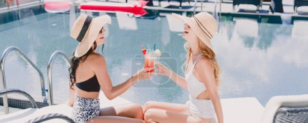 Foto de Two beautiful friends laughing and clinking with cocktails near swimming pool - Imagen libre de derechos