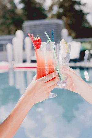 Photo for Cropped view of women clinking with glasses of cocktail near swimming pool - Royalty Free Image