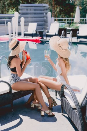 Photo for Back view of two women in straw hats sitting on loungers near swimming pool and drinking cocktails - Royalty Free Image