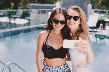 Photo for Smiling blonde and brunette friends in sunglasses and swimsuits taking selfie near swimming pool - Royalty Free Image