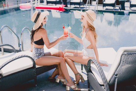 Photo for Blonde and brunette women in straw hats and swimsuits clinking with cocktails near swimming pool - Royalty Free Image
