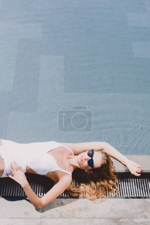 Photo for Sexy blonde woman in sunglasses and white swimsuit lying near swimming pool - Royalty Free Image
