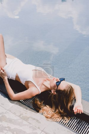 Photo for Sexy blonde woman in sunglasses and white swimsuit lying near swimming pool under sunshine - Royalty Free Image
