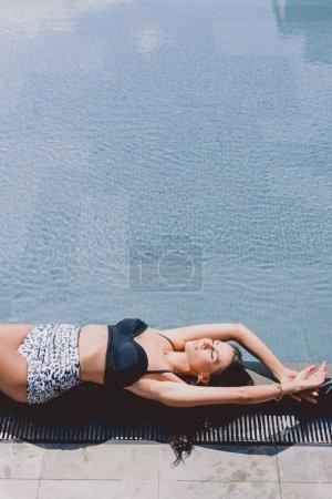 Foto de Sexy smiling brunette woman in swimsuit lying with closed eyes near swimming pool - Imagen libre de derechos