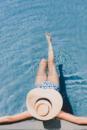 Photo for Overhead view of young woman in straw hat resting in swimming pool - Royalty Free Image