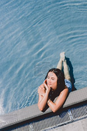 Photo for Beautiful brunette wet woman with closed eyes sunbathing in water in swimming pool - Royalty Free Image