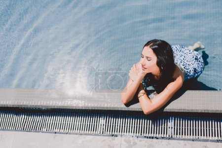 Photo for Attractive brunette wet woman with closed eyes sunbathing in water in swimming pool - Royalty Free Image