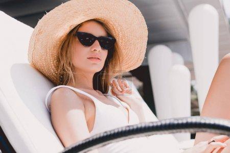 Photo pour Belle femme blonde dans le chapeau de paille et les lunettes de soleil bronzer sur le transat - image libre de droit