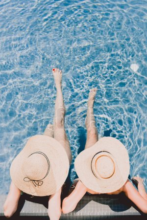 Photo for Top view of two women in straw hats relaxing in swimming pool - Royalty Free Image