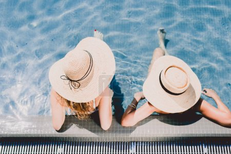 Photo for Overhead view of two women in straw hats relaxing in swimming pool - Royalty Free Image
