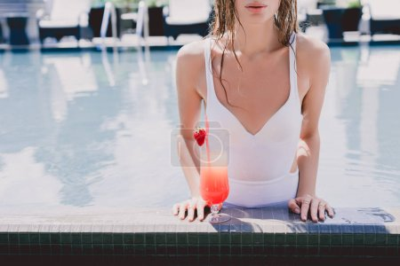 Photo for Cropped view of wet woman in swimming pool with cool strawberry cocktail - Royalty Free Image