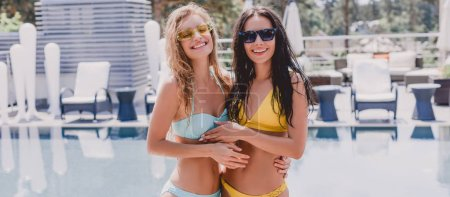 Photo for Happy friends in swimsuits hugging near swimming pool - Royalty Free Image