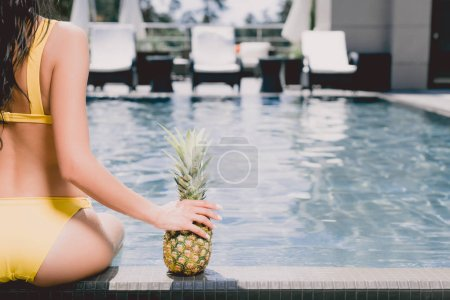 Photo for Cropped view of woman in swimsuit sitting near swimming pool and holding ripe pineapple - Royalty Free Image