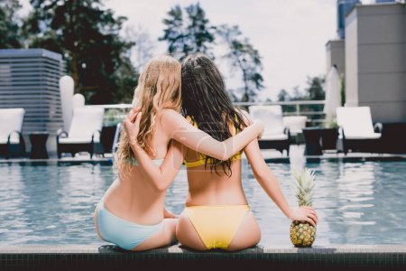 Photo for Back view of blonde and brunette wet girls hugging near swimming pool near pineapple - Royalty Free Image