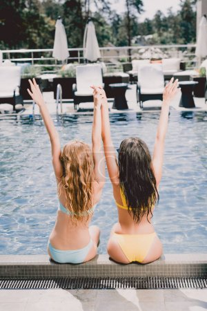 Photo for Back view of blonde and brunette girls sitting near swimming pool with hands in air - Royalty Free Image