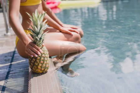 Photo for Selective focus of girl sitting friend with pineapple near swimming pool - Royalty Free Image