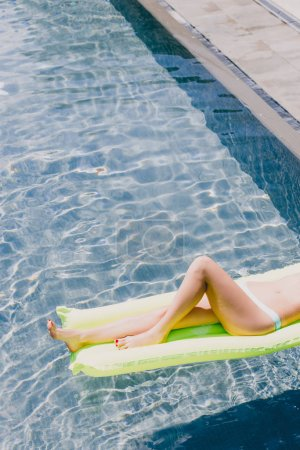Photo for Cropped view of sexy slim woman in swimsuit swimming on green pool float in swimming pool - Royalty Free Image