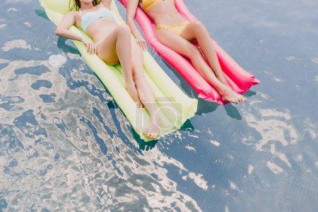 Photo pour Vue recadrée des filles dans des maillots de bain se trouvant sur des flotteurs de piscine dans la piscine - image libre de droit