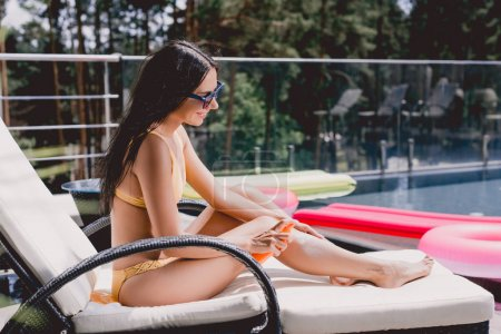 Photo for Sexy brunette woman in swimsuit applying sunscreen on body while sunbathing on sunbed - Royalty Free Image