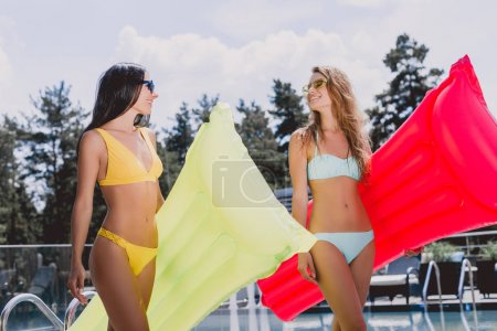 Photo for Low angle view of happy blonde and brunette girls in swimsuits and sunglasses walking with inflatable pool floats and looking at each other - Royalty Free Image