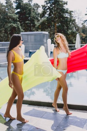 Photo for Happy blonde and brunette sexy girls in swimsuits and sunglasses walking with inflatable pool floats and looking at each other - Royalty Free Image