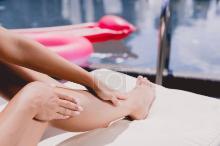 Photo for Partial view of woman applying sunscreen on leg while sunbathing near swimming pool - Royalty Free Image