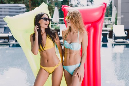 Photo for Happy blonde and brunette girls in swimsuits and sunglasses with inflatable pool floats laughing and looking at each other - Royalty Free Image