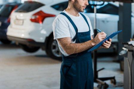 Photo pour Vue recadrée de l'écriture de mécanicien de voiture tout en retenant le presse-papiers près des voitures - image libre de droit