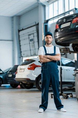Photo pour Beau mécanicien de voiture restant avec les bras croisés près des voitures - image libre de droit
