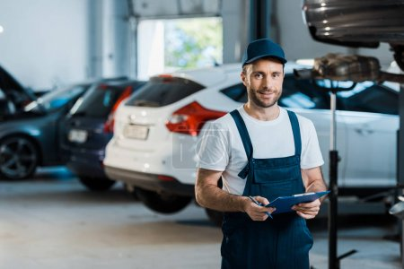 happy bearded car mechanic looking at camera and holding clipboard near cars