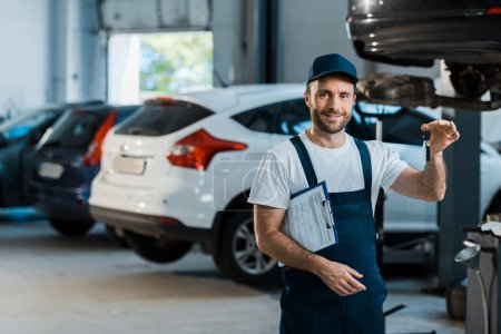 Photo for Happy bearded car mechanic looking at camera and holding clipboard and key near cars - Royalty Free Image