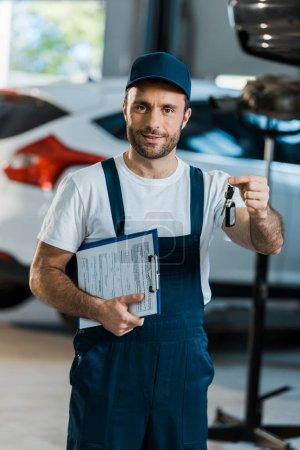 Photo pour Mécanicien de voiture heureux regardant l'appareil-photo et le presse-papiers de fixation et la clef près de la voiture - image libre de droit