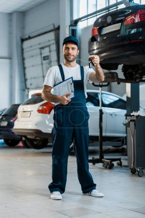 Photo for Happy car mechanic looking at camera and holding clipboard and key near cars - Royalty Free Image