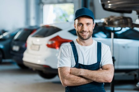 Photo for Happy car mechanic standing with crossed arms in car service - Royalty Free Image