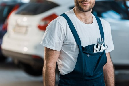 Photo for Cropped view of happy car mechanic standing with hand wrenches in pocket - Royalty Free Image