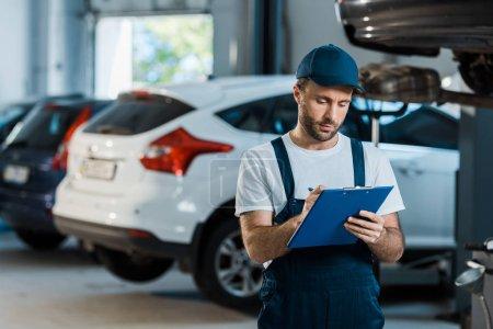 Photo pour Mécanicien de voiture barbu écrivant tout en retenant le presse-papiers près des voitures - image libre de droit