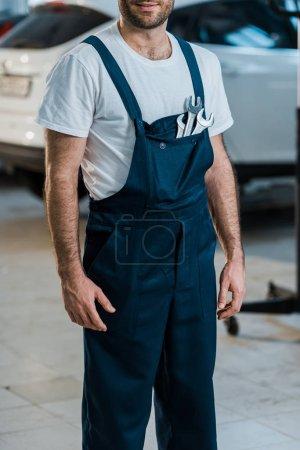 Photo pour Vue recadrée de mécanicien automatique heureux restant avec des clés de main dans la poche - image libre de droit