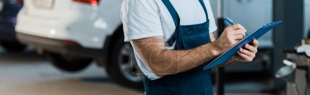 Photo pour Tir panoramique de mécanicien de voiture écrivant tout en retenant le presse-papiers près de la voiture - image libre de droit