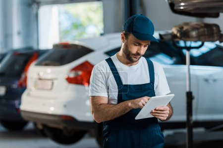 Photo for Bearded car mechanic in cap using digital tablet near cars - Royalty Free Image