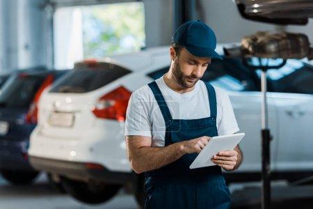 Photo pour Mécanicien de voiture barbu dans le chapeau utilisant la tablette numérique près des voitures - image libre de droit