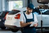 bearded car mechanic in cap using digital tablet near cars