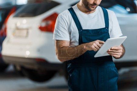 Photo pour Vue recadrée du mécanicien de voiture en utilisant la tablette numérique dans le service de voiture - image libre de droit