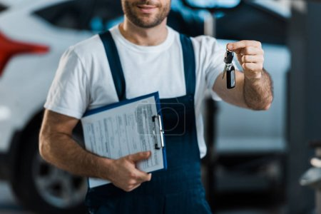 cropped view of car mechanic holding clipboard and key