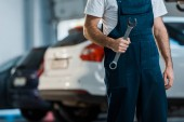 cropped view of car mechanic holding hand wrench in car service