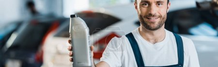Photo for Panoramic shot of happy car mechanic holding bottle with car oil - Royalty Free Image